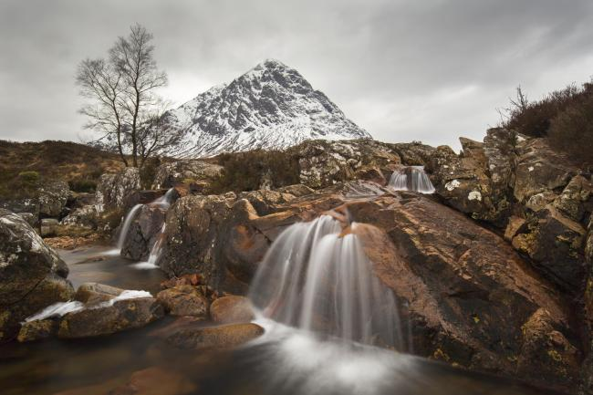 Scottish mountain Buachaille Etive Mor and waterfall on River Coupall in winter in Glen Etive near Glencoe in the Highlands of Scotland, UK. (Photo by: Arterra/UIG via Getty Images)