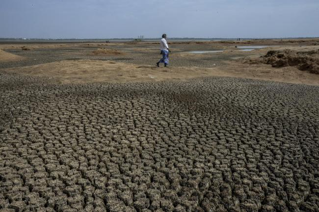 CHENNAI, INDIA - JUNE 28: Locals walk in dry bed of Chembarambakkam lake on June 28, 2019 in the outskirts of Chennai, India. All the four major reservoirs supplying water to Chennai has dried up and the only hope for the city to tide over the water crisi