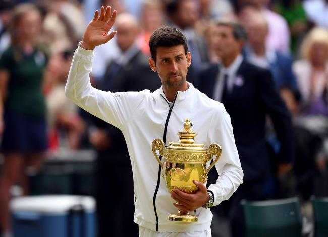 Novak Djokovic with the trophy after beating Roger Federer in the mens singles final on day thirteen of the Wimbledon Championships at the All England Lawn Tennis and Croquet Club, Wimbledon. PRESS ASSOCIATION Photo. Picture date: Sunday July 14, 2019. Se