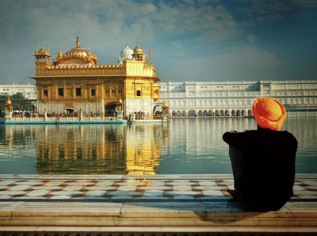 Sikh devotee sitting by the Pool of Nectar, The Golden Temple, Amritsar, India.