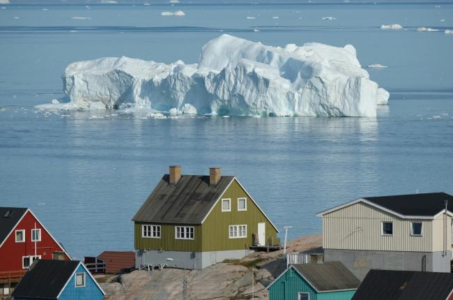 An iceberg floats in Disko Bay behind houses during unseasonably warm weather on July 30, 2019 in Ilulissat, Greenland. The Sahara heat wave that recently sent temperatures to record levels in parts of Europe