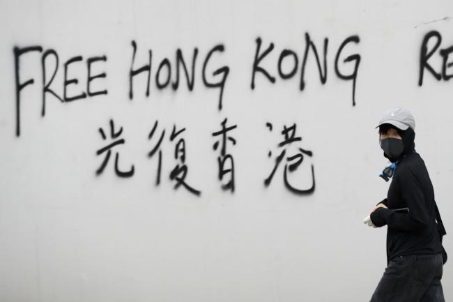 A protester spray-paints a slogan on a wall during a demonstration in Hong Kong, Saturday, Aug. 3, 2019. Hong Kong protesters ignored police warnings and streamed past the designated endpoint for a rally Saturday in the latest of a series of demonstration