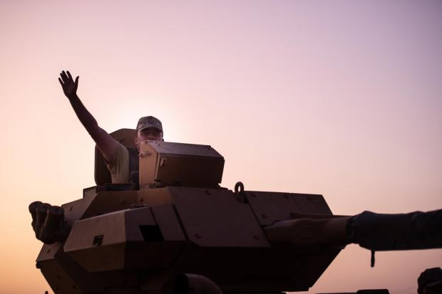 HeraldScotland: A Turkish soldier waves on the top of an armored vehicle as the troops prepare to cross the border into Syria on October 09, 2019 in Akcakale, Turkey. The military action is part of a campaign to extend Turkish control of more of northern Syria, a large sw ath of w hich is currently held by Syrian Kurds, w hom Turkey regards as a threat. U.S. President Donald Trump granted tacit American approval to this campaign, w ithdraw ing his country's troops from several Syrian outposts near the Turkish border. Photo by Burak Kara, Getty