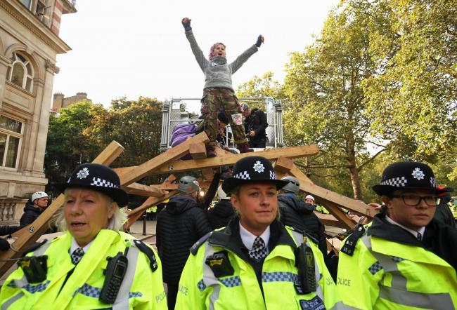 A protester on a wooden structure on Birdcage Walk, outside the Institute of Mechanical Engineers, during the third day of an Extinction Rebellion (XR) protest in Westminster, London. PA Photo. Picture date: Wednesday October 9, 2019. See PA story ENVIRON