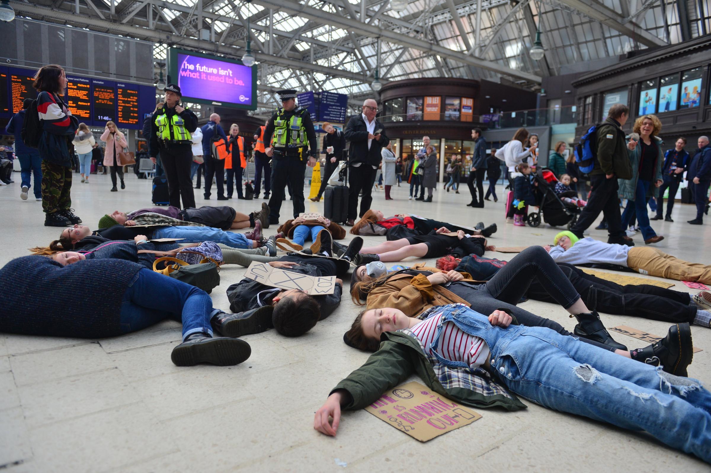 Extinction Rebllion stage 'die in' at Glasgow train station