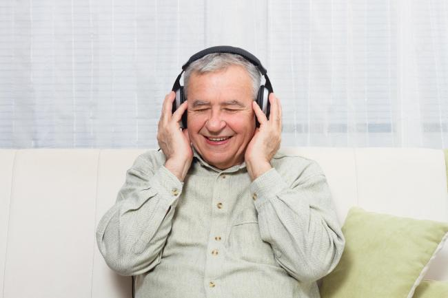 Senior man sitting on  sofa with headphones  and enjoys listening music..