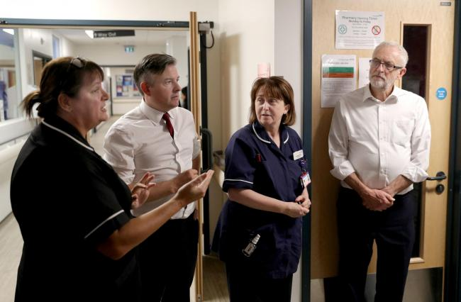 Labour Party leader Jeremy Corbyn (right) and shadow heath secretary Jonathan Ashworth listen as Julia Fairhall, Area Head of Nursing and Governance at Sussex Community NHS Foundation Trust, speaks during their visit to Crawley Hospital, Crawley, West Sus