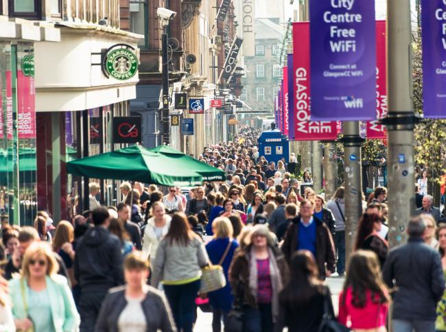 Crowds of people passing shops and businesses on Buchanan Street, one of Glasgow's busiest shopping streets..