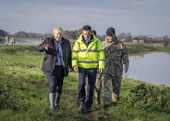 Boris Johnson is given a briefing by Lt Col Tom Robinson of the Light Dragoons and Oliver Harmar, of the Environment Agency, as he visits flooded Stainforth.