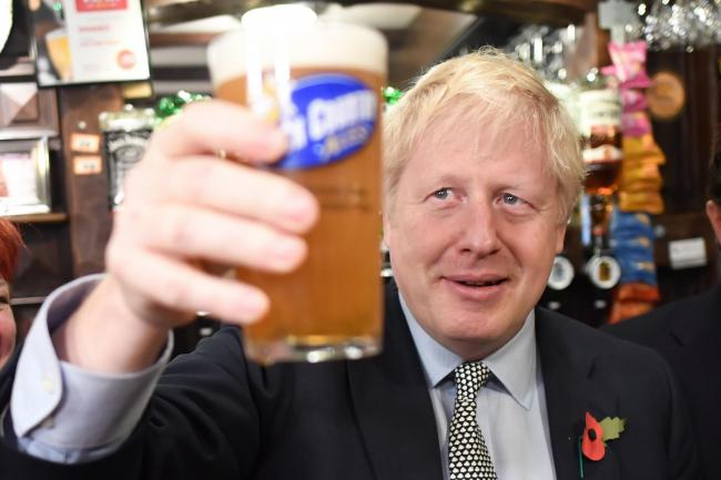 Prime Minister Boris Johnson, raises a pint as he meets with military veterans at the Lych Gate Tavern in Wolverhampton. PA Photo. Picture date: Monday November 11, 2019. See PA story POLITICS Election. Photo credit should read: Stefan Rousseau/PA Wire.