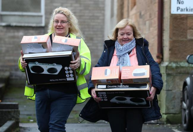 People leave Camelon community centre in Falkirk with hot plates and fan heaters after homes in the area were affected by a gas mains failure. PA Photo. Picture date: Monday December 2, 2019. Gas network company SGN is working to restore supplies to arou
