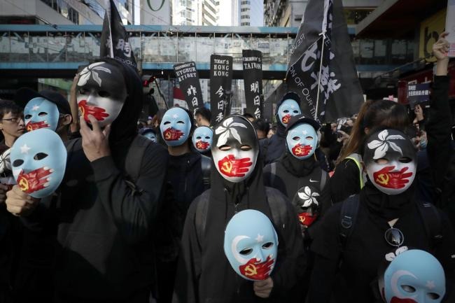 Masked pro-democracy protesters march on a street in Hong Kong, Sunday, Dec. 8, 2019. Marchers are again expected to fill Hong Kong streets Sunday in a rally that will test the enduring appeal of an anti-government movement marking a half year of demonst