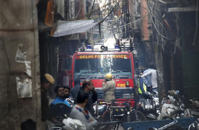 A fire engine stands by the site of a fire in an alleyway, tangled in electrical wire and too narrow for vehicles to access, in New Delhi, India, Sunday, Dec. 8, 2019. Dozens of people died on Sunday in a devastating fire at a building in a crowded grain