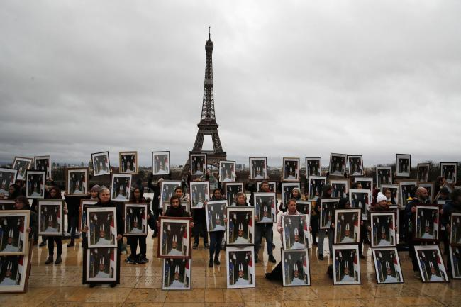 A hundred activists hold portraits of President Emmanuel Macron to urge France to take action during the U.N. COP 25 climate talks in Madrid, during a gathering at Place du Trocadero facing the Eiffel Tower in Paris, Sunday, Dec. 8, 2019. Environmental a