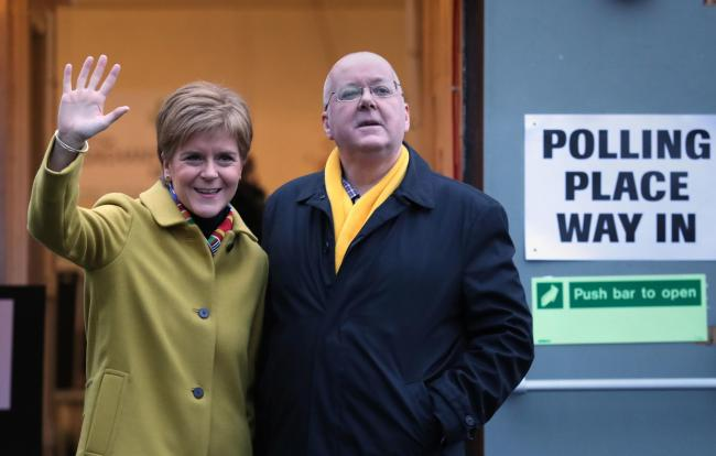 SNP leader Nicola Sturgeon with husband Peter Murrell as they cast their votes in the 2019 General Election at Broomhouse Park Community Hall in Glasgow. PA Photo. Picture date: Thursday December 12, 2019. See PA story POLITICS Election. Photo credit shou