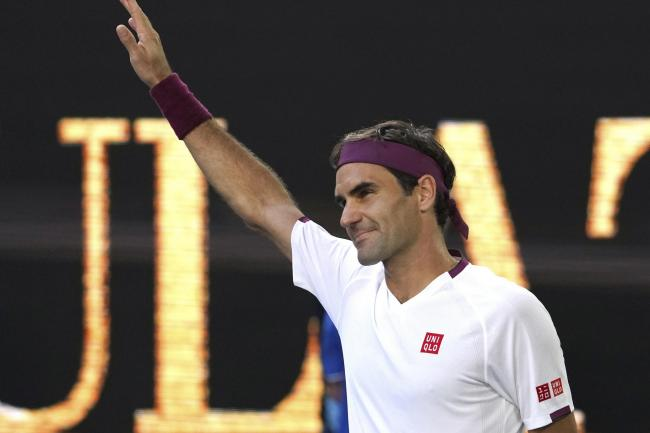 Roger Federer holds his arm aloft after beating Tennys Sandgren