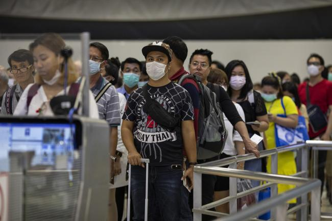 As Coronavirus spreads travelers arriving wait in line at immigration wear masks at Suvarnabhumi International airport  in Bangkok, Thailand. Photo by Paula Bronstein/Getty Images.