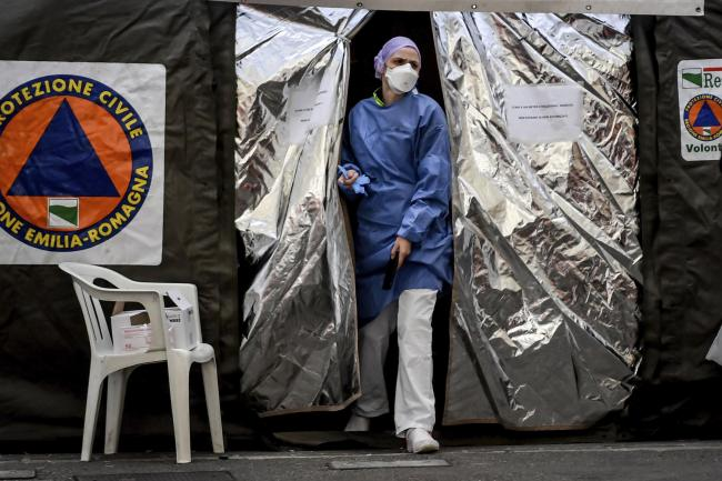A paramedics wearing a mask gets out of a tent set up by the Italian Civil Protection outside the emergency ward of the Piacenza hospital, northern Italy, Thursday, Feb. 27, 2020. Italy is changing how it reports coronavirus cases and who will get tested