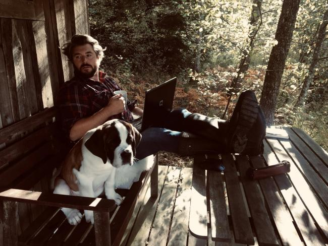 British novelist and father Will Dean, who lives in the middle of a Swedish elk forest, relaxes with his dog Bernie the Saint Bernard.
