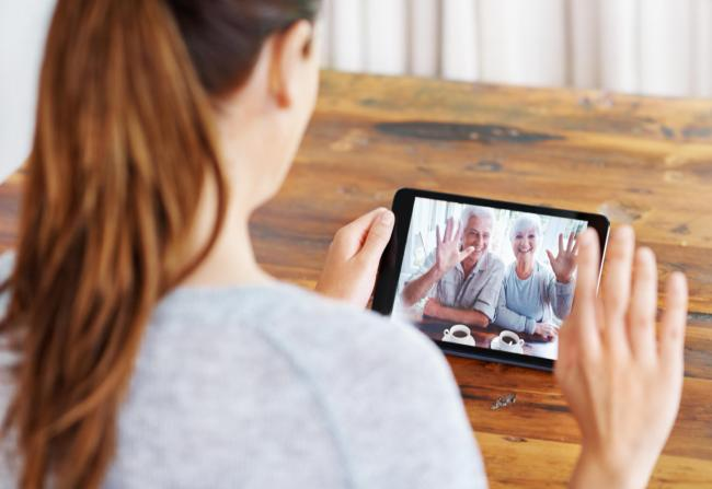 A young woman using a digital tablet for a video call with her family.
