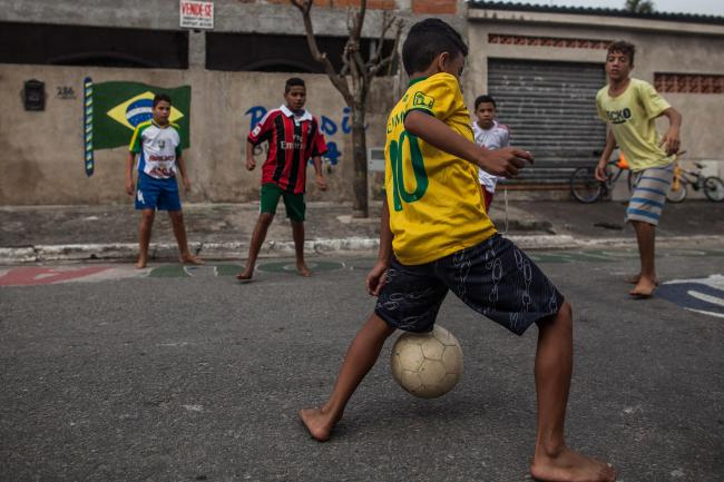 Boys play football  in the streets of the Garden Gloria neighborhood in the city of Praia Grande