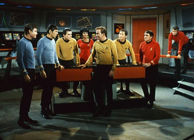 Deforest Kelley, from left, Leonard Nimoy, Walter Koenig, Nichelle Nichols, Williams Shatner, George Takei, James Doohan and an unidentified actor appear in a scene from the television series Star Trek.