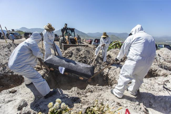 Cemetery workers wearing PPE take a coffin containing a victim of Covid-19 to a tomb in Tijuana, Mexico.