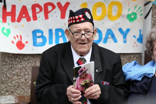 Former Royal Scots George Simpson outside his house in Danderhall, Midlothian, with his card from the Queen, to mark his 100th birthday (Image: PA)
