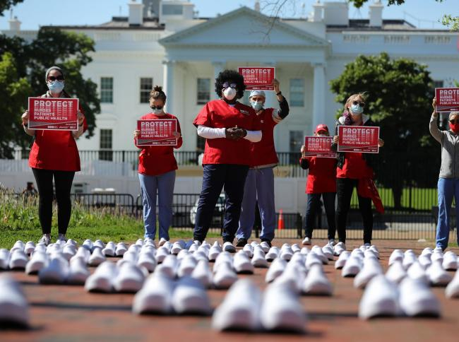 Members of the National Nurses United stand in protest among empty shoes representing nurses that they say have died from Covid-19 in Lafayette Park across from the White House in Washington, USA.