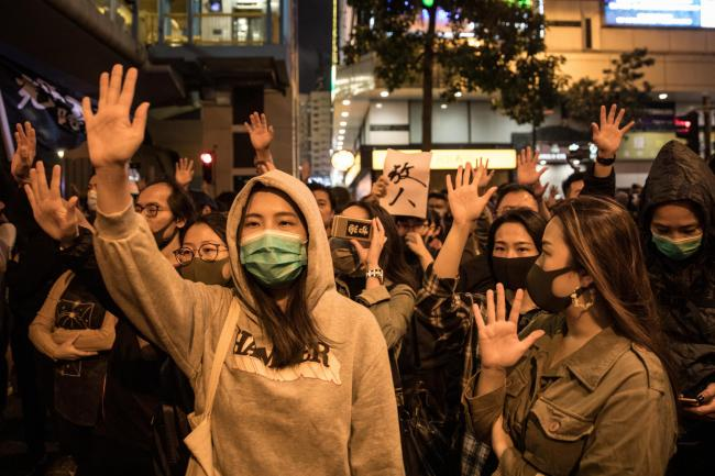 HONG KONG, CHINA - NOVEMBER 25: Anti-government protesters chant slogans and wave flags at police after gathering in front of an entrance to the Hong Kong Polytechnic University where a small number of protesters are held up inside on November 25, 2019 in