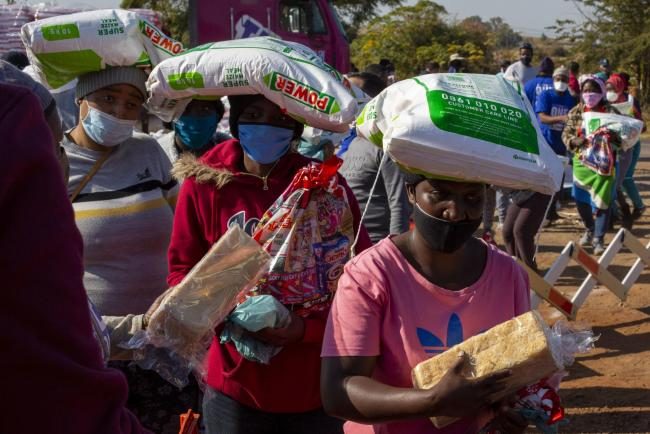 People affected by the coronavirus economic downturn, receive food donations at the Iterileng informal settlement near Laudium, southwest of Pretoria, South Africa, Wednesday, May 20, 2020. (AP Photo/Themba Hadebe).