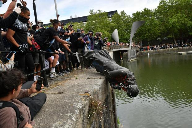 HeraldScotland: Protesters throw a statue of slave trader Edward Colston into Bristol harbour during a Black Lives Matter protest rally. Picture: Ben Birchall/PA