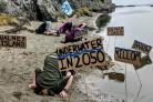 Campaigners bury their heads in sand in protest at planned mine near Whitehaven.