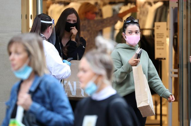 People wear a mask as they leave a shop in Buchanan Street in Glasgow as it became compulsory to wear face coverings in shops from today as Scotland continues with the gradual lifting of restrictions to ease out of lockdown.
