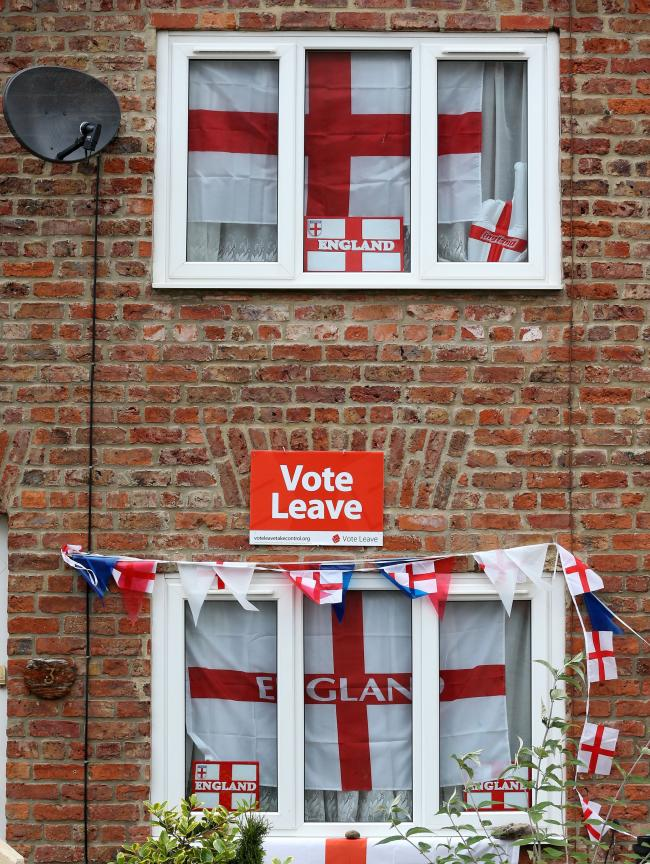 "English Cross of St George flags hang in the windows and a ""Vote Leave"" poster is displayed on a house in Redcar, north east England on June 27, 2016.Britain's historic decision to leave the 28-nation bloc has sent shockwaves through the pol"
