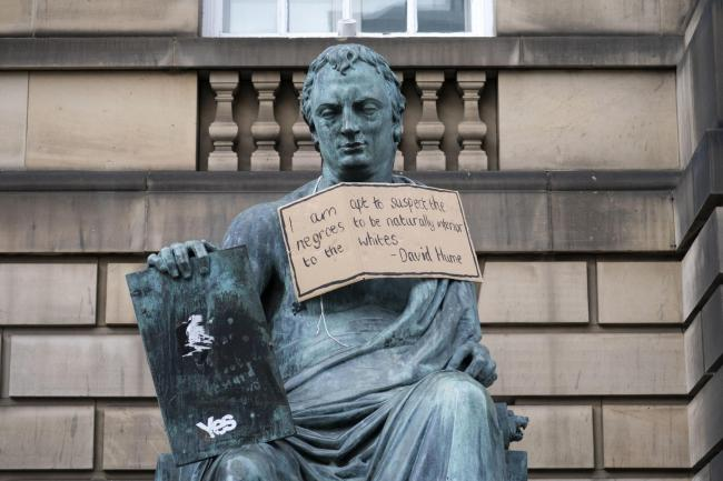 A poster hangs from the statue of the 18th Century philosopher David Hume on the Royal Mile, Edinburgh, following the Black Lives Matter protest rally on June 7, 2020, in Holyrood Park, Edinburgh, in memory of George Floyd who was killed on May 25 while i