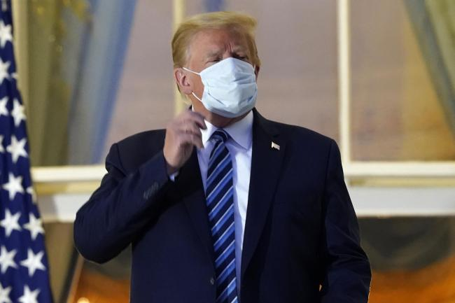 President Donald Trump removes his mask as he stands on the balcony outside of the Blue Room as returns to the White House Monday, Oct. 5, 2020, in Washington, after leaving Walter Reed National Military Medical Center, in Bethesda, Md. Trump announced he