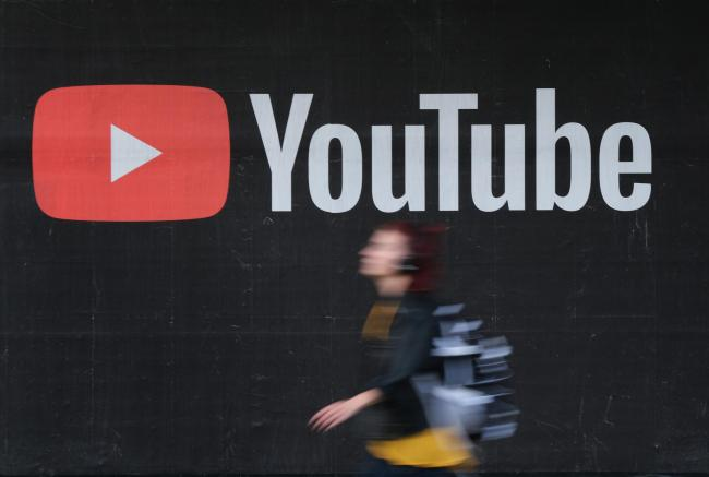 A young woman walks past a billboard advertisement for YouTubePicture: Getty Images
