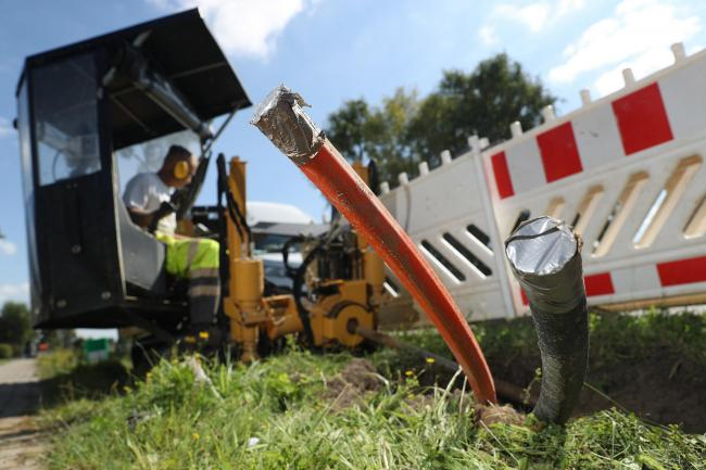 HALDENSLEBEN, GERMANY - AUGUST 23:  A worker uses a specialized drilling vehicle for digging a horizontal hole to accomodate tubing used for laying fiber optic cable underground during the installation of broadband infrastructure in the village of Beberta