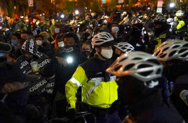 Police patrol as demonstrators march through streets near the White House (Photo: AP)
