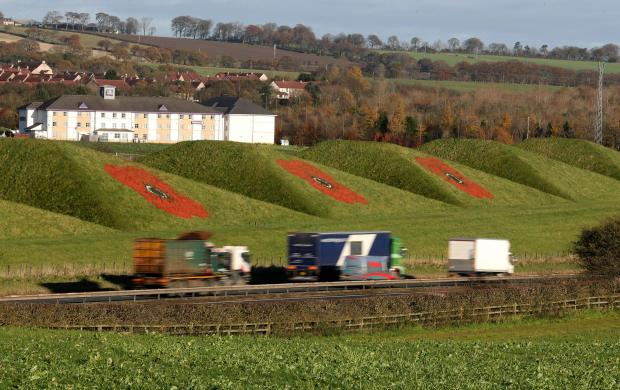 HeraldScotland: Giant poppies painted on the side of the Bathgate Pyramids next to the M8 in West Lothian ahead of Remembrance Sunday.