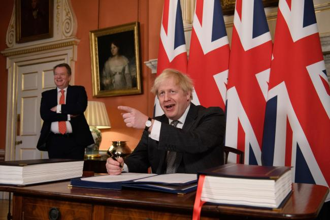 UK chief trade negotiator, David Frost looks on as Prime Minister Boris Johnson signs the EU-UK Trade and Cooperation Agreement at 10 Downing Street, Westminster. Photo credit should read: Leon Neal/PA Wire.
