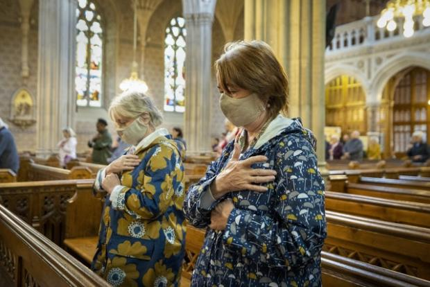 HeraldScotland: Parishioners wearing face masks bless themselves at the end of mass (Liam McBurney/PA)