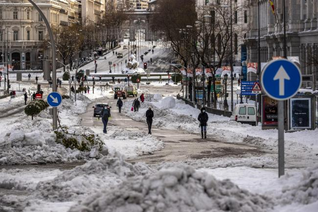 People walk through snow in downtown Madrid, Spain, Sunday, Jan. 10, 2021. A large part of central Spain including the capital of Madrid are slowly clearing snow after the country's worst snowstorm in recent memory. (AP Photo/Manu Fernandez)