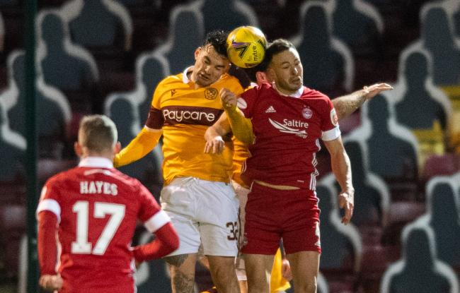 Tony Watt of Motherwell and Aberdeen's Andy Considine contest a header