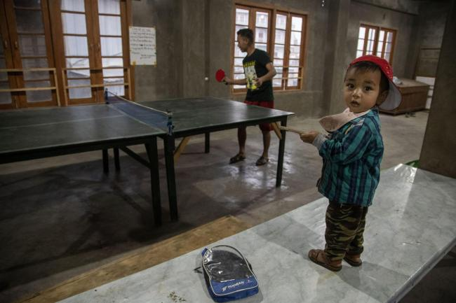 A police officer who fled Myanmar following a military coup plays table tennis at an undisclosed place in Mizoram, a state bordering Myanmar, India, Friday, March 19, 2021. Several Myanmar police officers who fled to India after defying army orders to