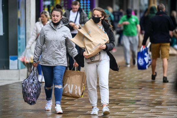 HeraldScotland: EDINBURGH, SCOTLAND - JUNE 29: Shoppers wearing face masks and carrying shopping bags walk along Princess Street as the Scottish Lockdown eases and shops reopen on June 29, 2020 in Edinburgh, Scotland. Shops with on-street access opened their doors as