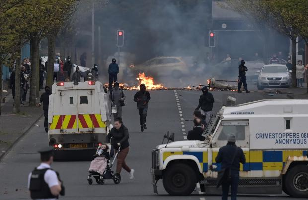 HeraldScotland: Loyalists clash with police on Lanark Way as they restart their protests against the Irish sea border and the NI Protocol on April 19, 2021 in Belfast, Northern Ireland. Loyalist tension has grown in the province following Brexit and the implementation of the NI Protocol, leading to violent clashes with police and nationalists in recent weeks.