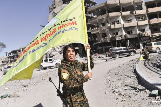 HeraldScotland: Rojda waves the SDF flag in Raqqa's Naim Square after leading the US-backed coalition, which included the YPJ, in its campaign to take the city from the Islamic State, October 2017 PHOTO: Getty Images