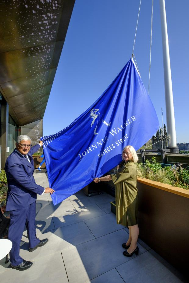 HeraldScotland: To mark the opening a Johnnie Walker flag was raised above the landmark building by Ivan Menezes, chief executive, Diageo, and Barbara Smith, managing director of Johnnie Walker Princes Street, against the Edinburgh backdrop.